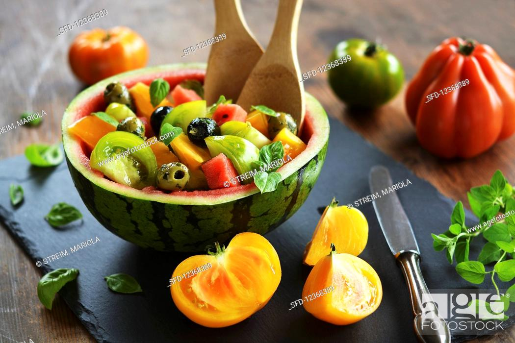 Photo de stock: Culinary watermelon, filled with salad of watermelon, colorful tomatoes, olives and fresh herbs.