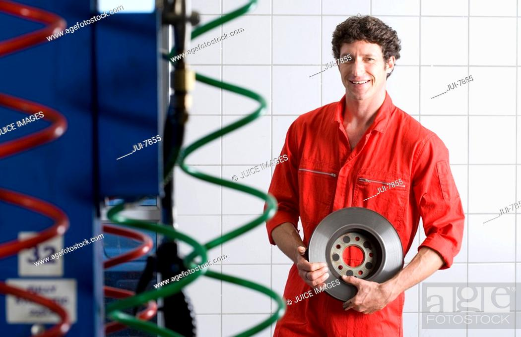 Stock Photo: Male car mechanic, in red overalls, standing in commercial garage, holding vehicle part, smiling, portrait.