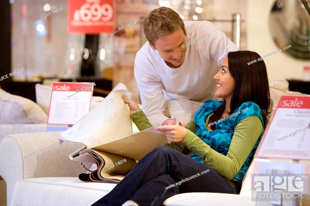 Stock Photo: Young couple with fabic samples in shop, smiling at each other.