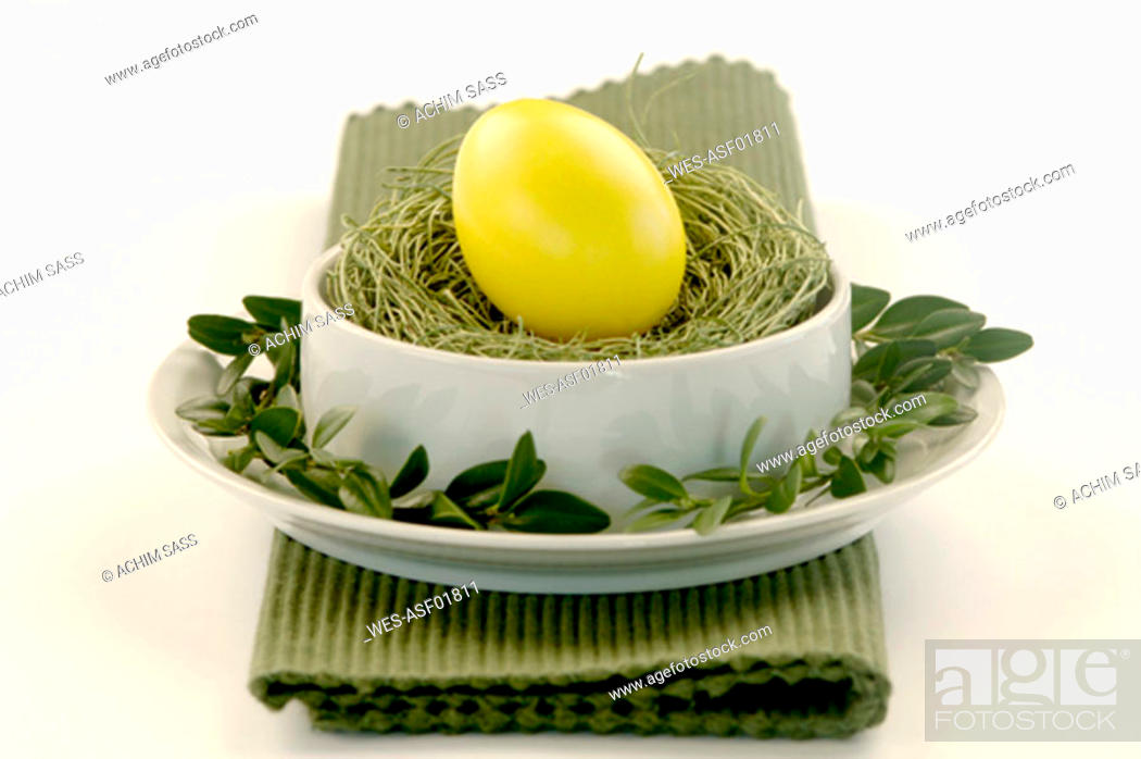 Stock Photo: Yellow Easter egg lying on grass in a bowl.