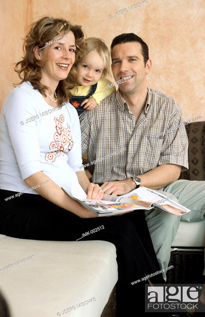 Stock Photo: A young couple, young man and young pregnant woman, 25-30 30-35 35-40 years old, sitting on the sofa with their little daughter, 1-5 years old.