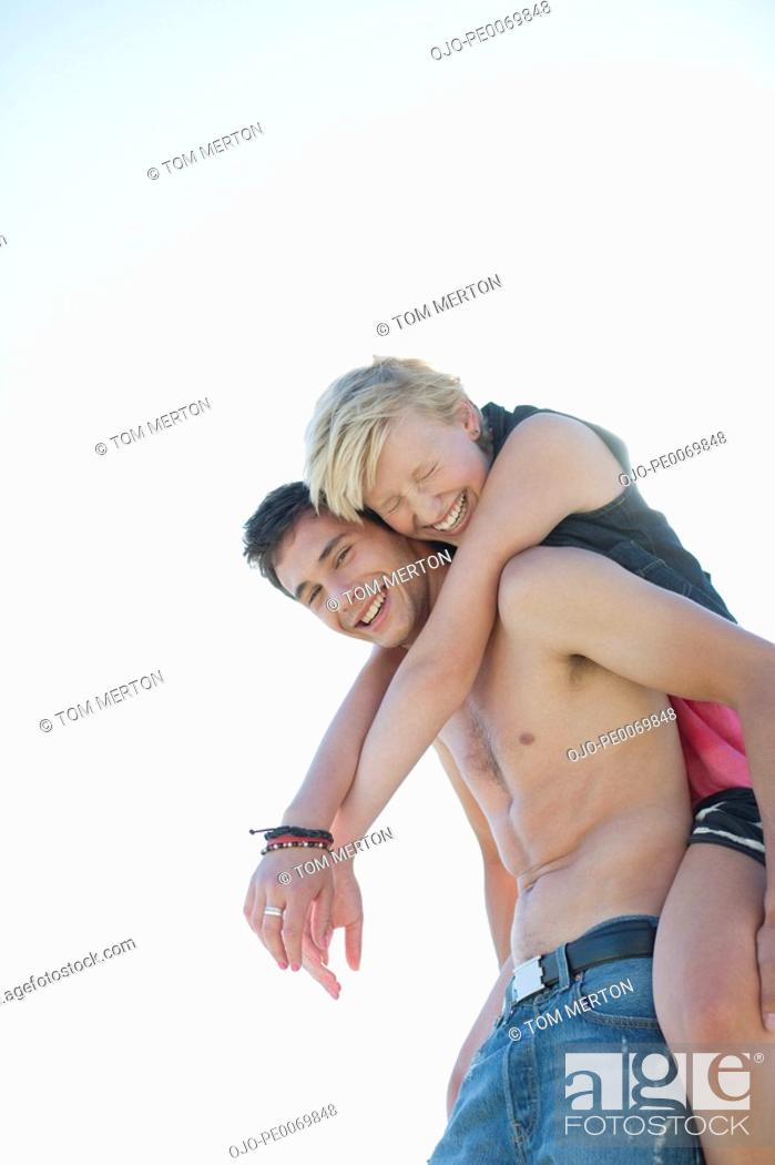 Stock Photo: Man with bare chest piggybacking woman.