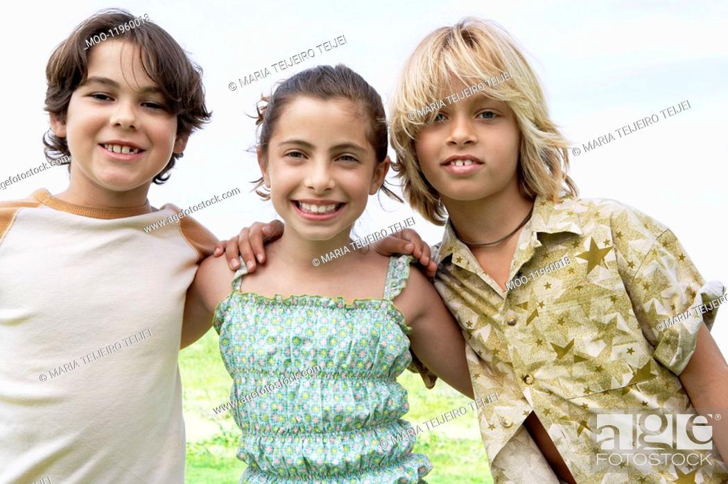 Stock Photo: Smiling pre-teen Friends standing side by side outside arms around.