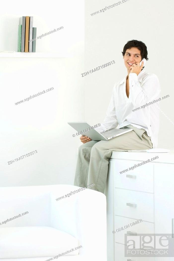 Stock Photo: Man sitting on counter, talking on landline phone, holding laptop on lap.