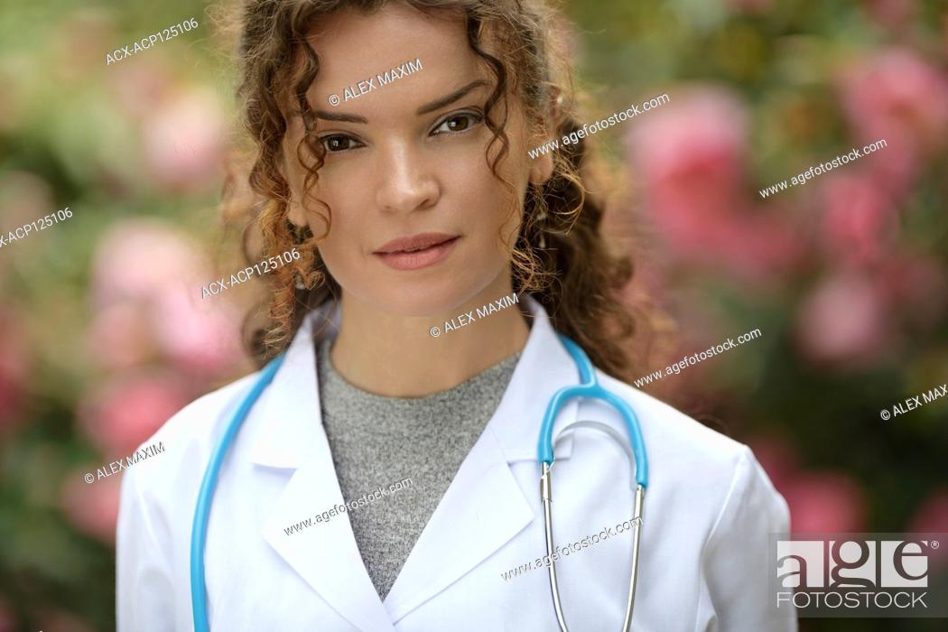 Stock Photo: Portrait of a young woman, medical practitioner, healthcare professional, doctor, physician wearing a lab coat in natural outdoor settings with blossoming.