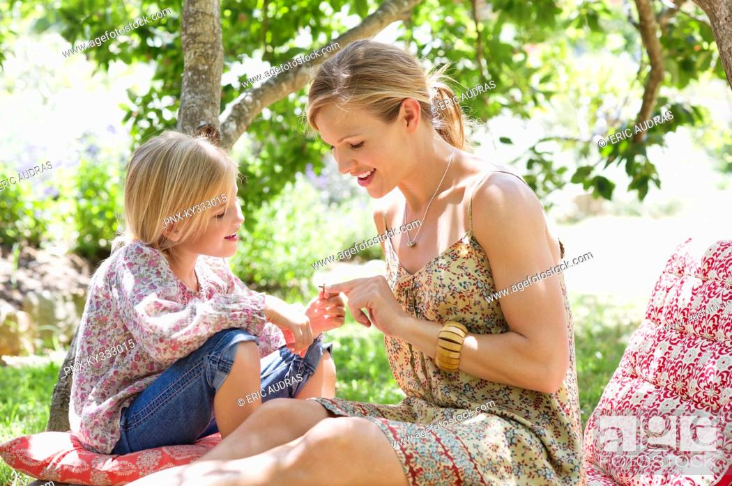 Stock Photo: Mother and a little girl sitting together outdoors.