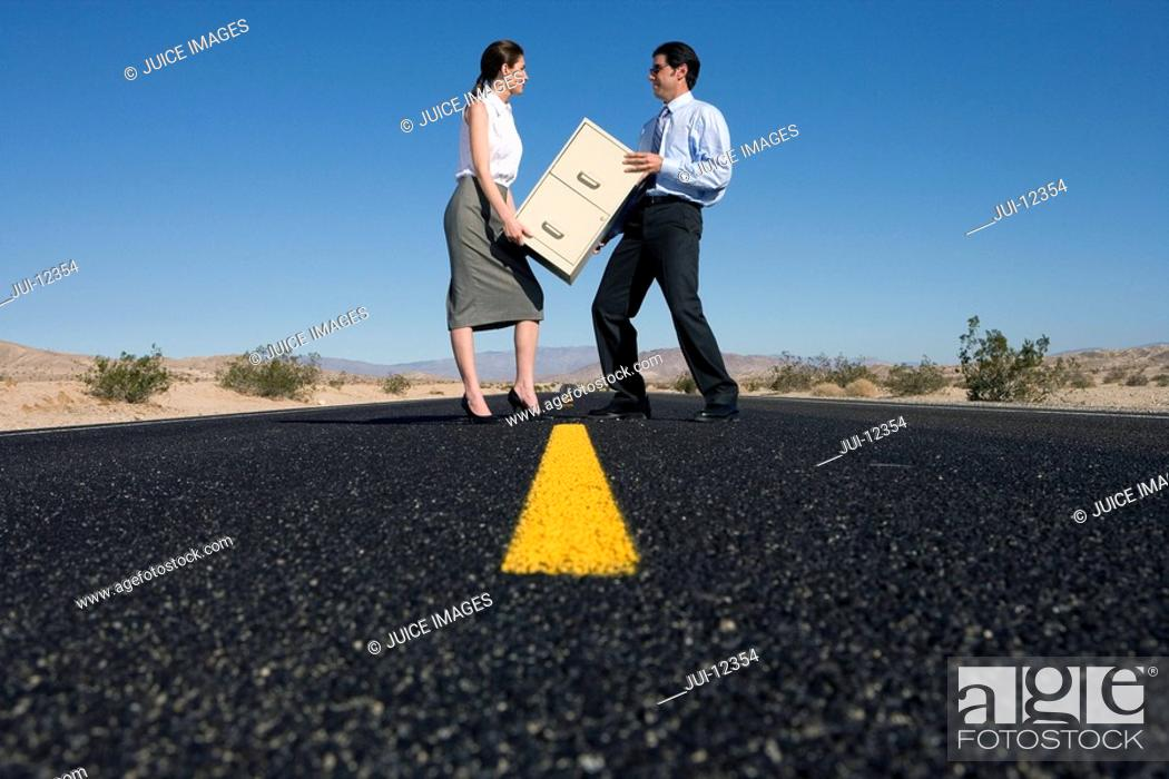 Stock Photo: Businessman and woman with filing cabinet on road in desert, low angle view.