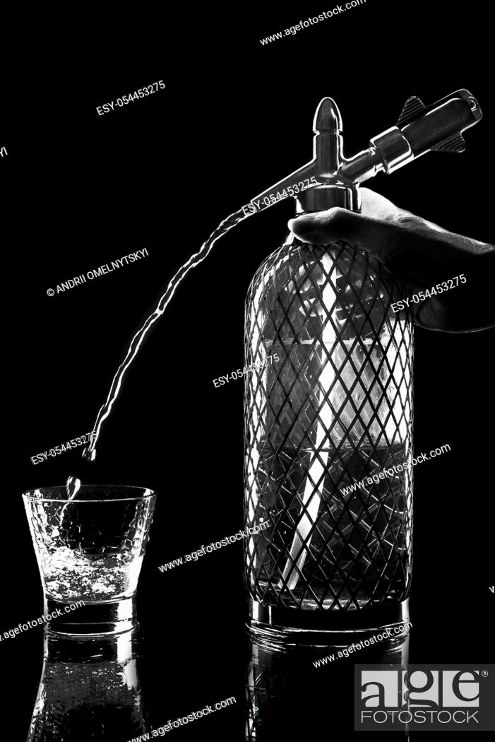 Stock Photo: siphon with soda copulation on the table on a black background with a full glass, jet and drops.
