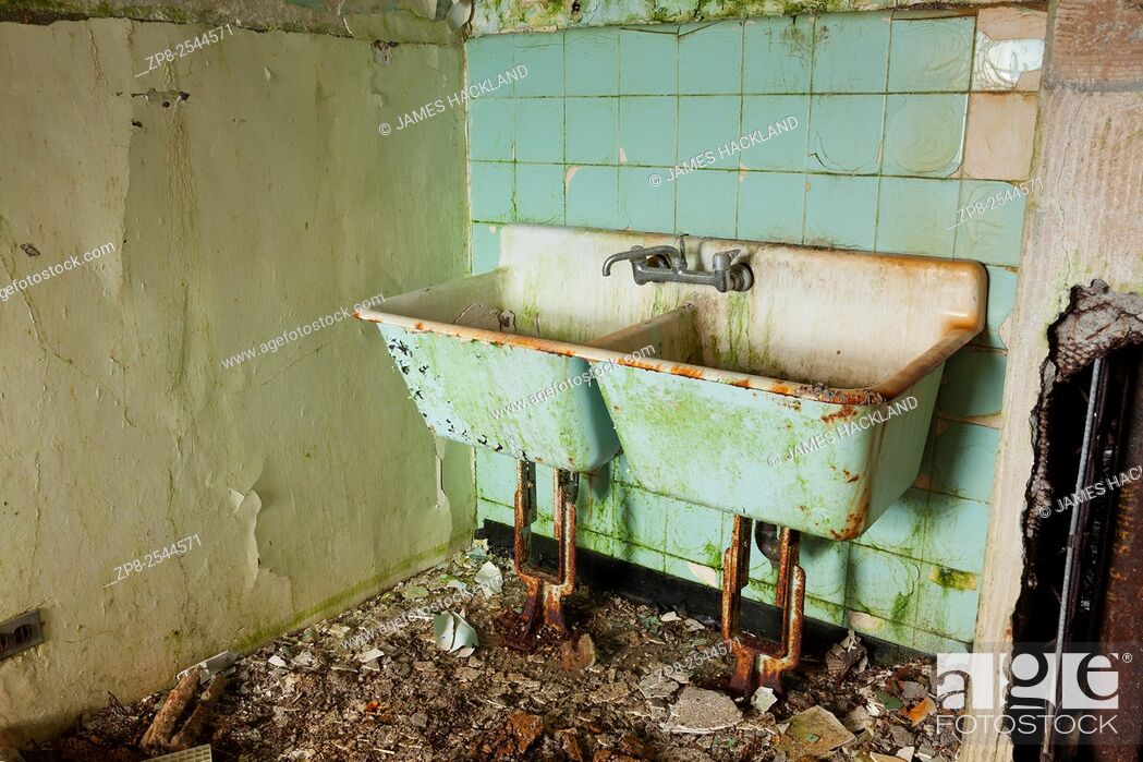 Stock Photo: A filthy, rusted old green laundry room sink found in an abandoned hospital in Canada.