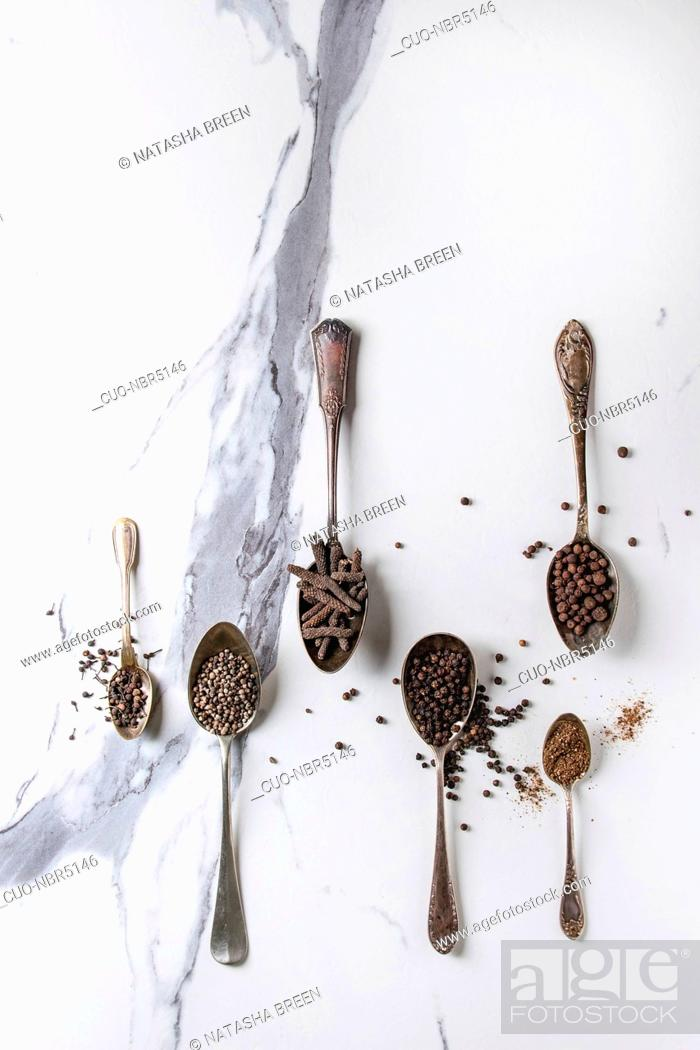 Stock Photo: Variety of different black peppers allspice, pimento, long pepper, monks pepper, peppercorns and ground powder in vintage spoons over white marble texture.