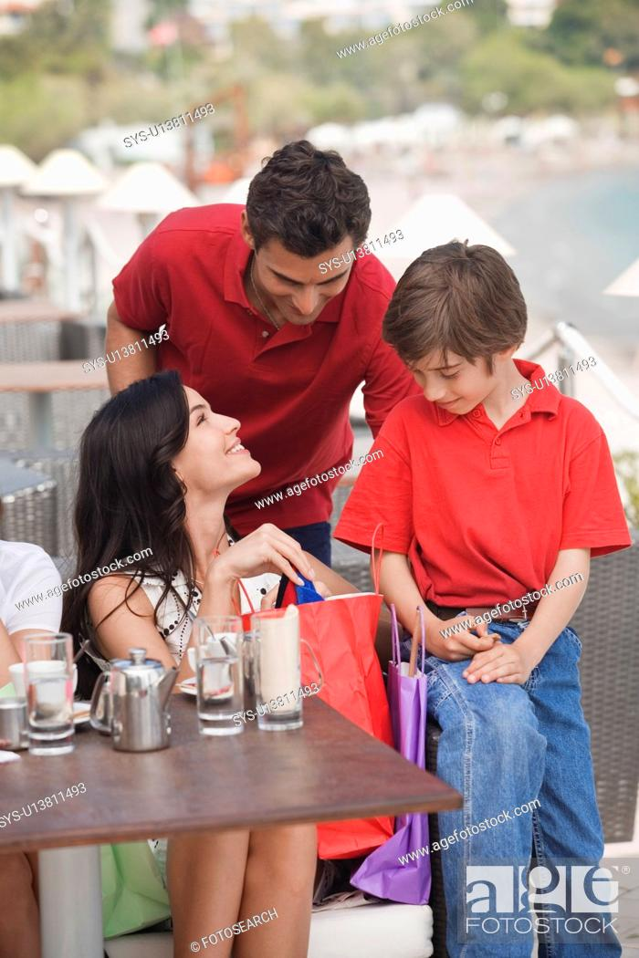 Stock Photo: Parents and son with shopping bags at a cafe.