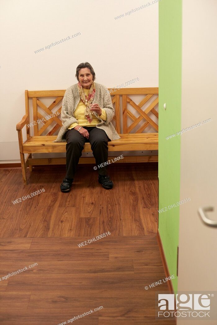 Stock Photo: Age demented senior woman sitting on bench in a nursing home.