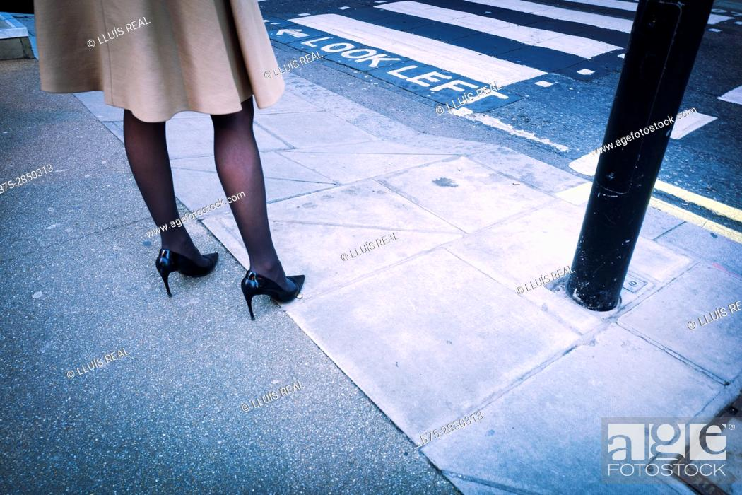 Stock Photo: Close-up of the legs of a woman dressed in fashion with a coat, black stockings and high heels in the street beside pedestrian crossing.