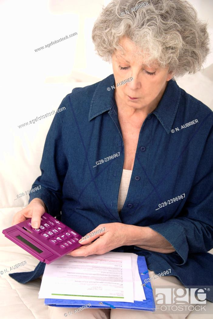 Stock Photo: Beautiful senior woman holding a pocket calculator and reading papers at home.