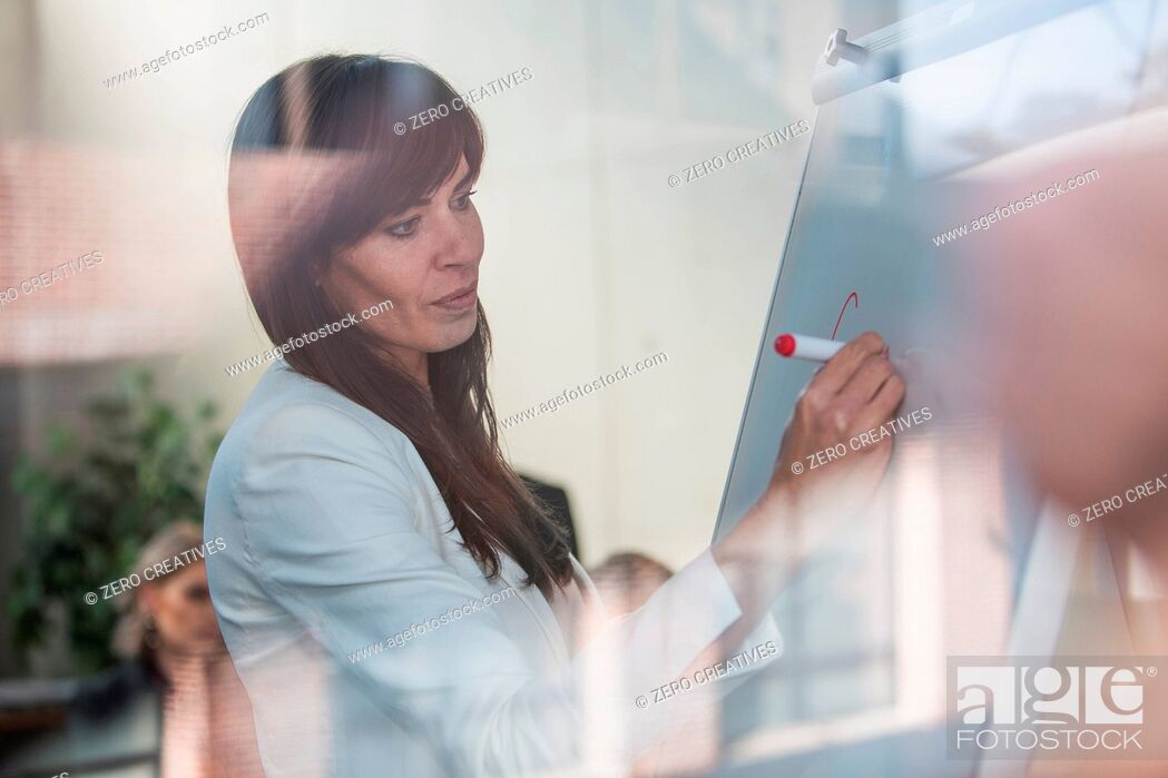 Stock Photo: Businesswoman writing on whiteboard in office.