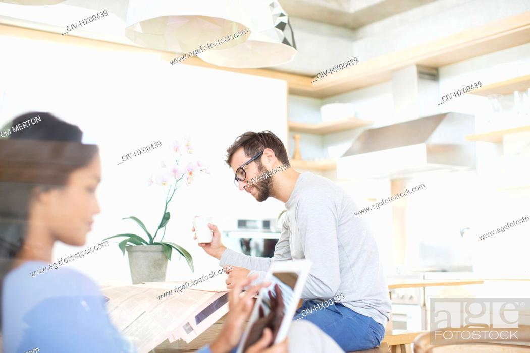 Stock Photo: Couple drinking coffee, reading newspaper and using digital tablet in kitchen.