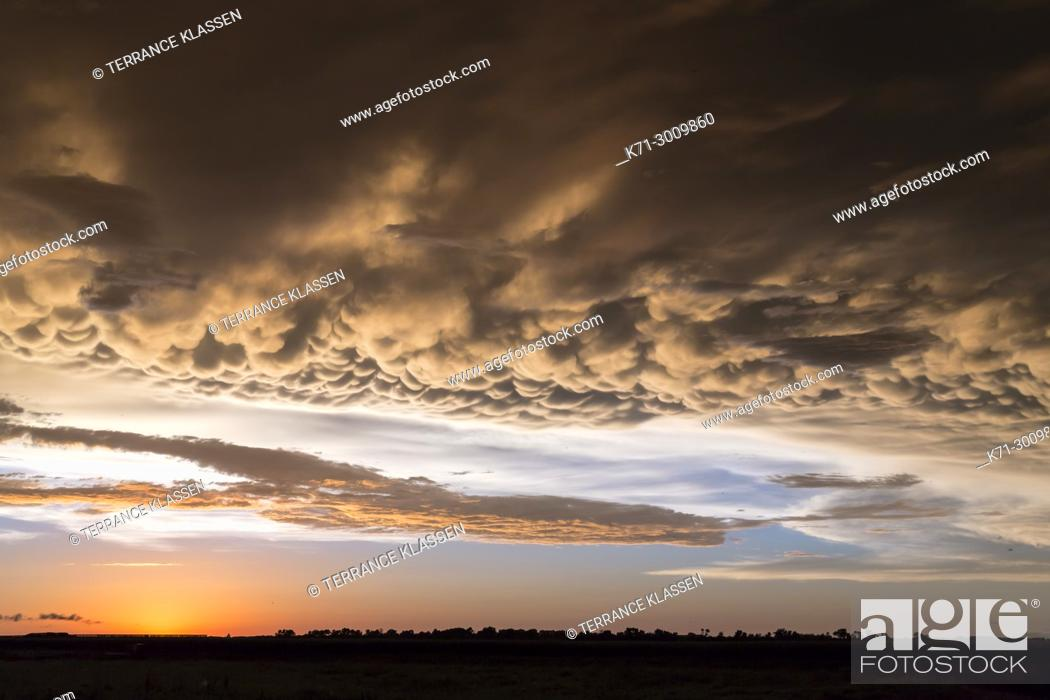 Imagen: A clearing storm and clouds on the prairies at sunset near Winkler, Manitoba, Canada.