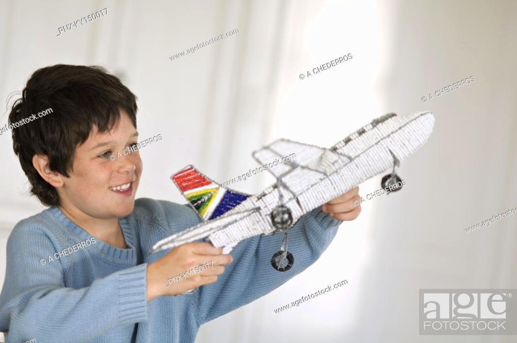 Stock Photo: Little boy playing with model aeroplane.