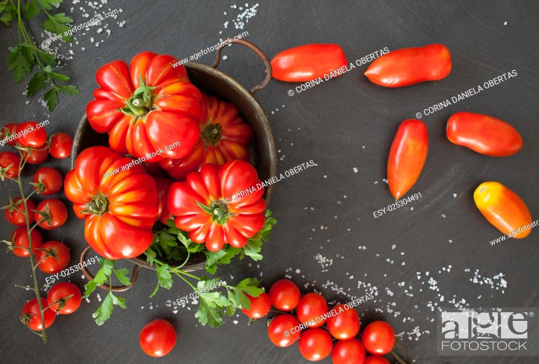 Photo de stock: Three different types of tomatoes on black background.