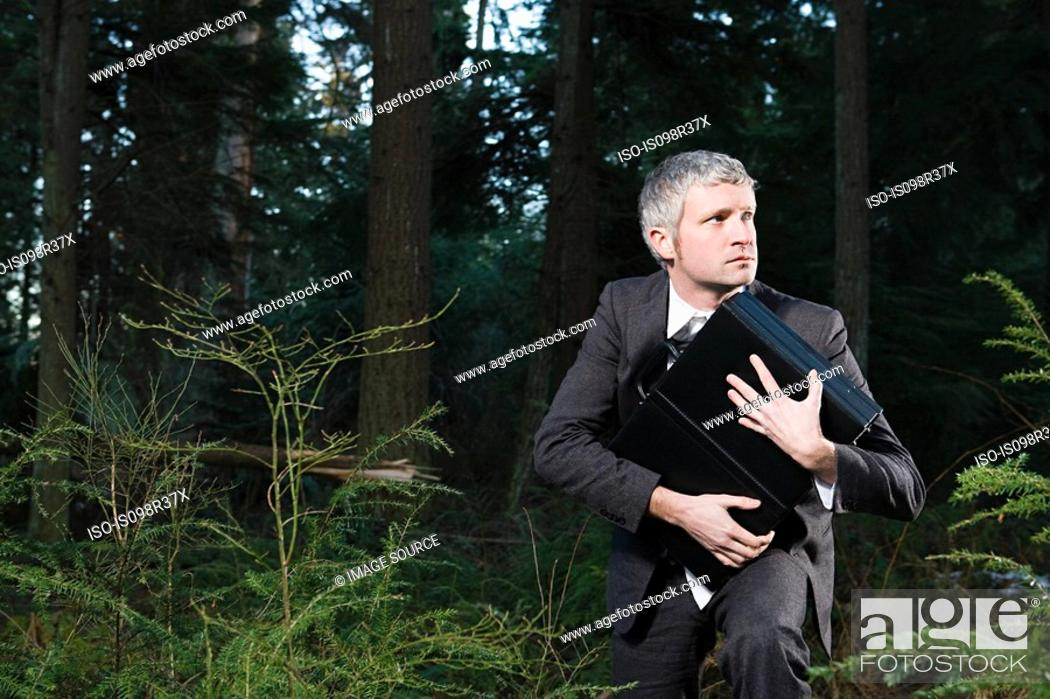 Stock Photo: Businessman in forest holding briefcase.
