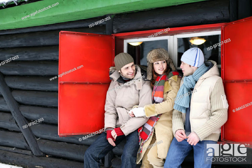 Stock Photo: Friends outside a wooden hut.