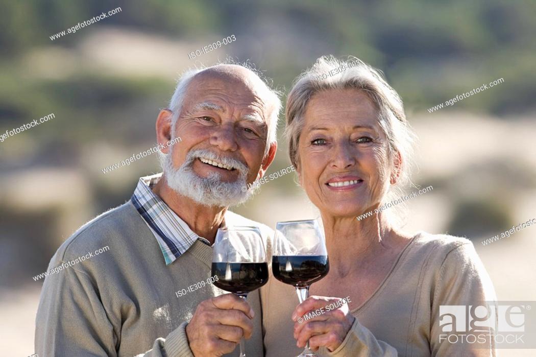 Stock Photo: Senior couple toasting with red wine.