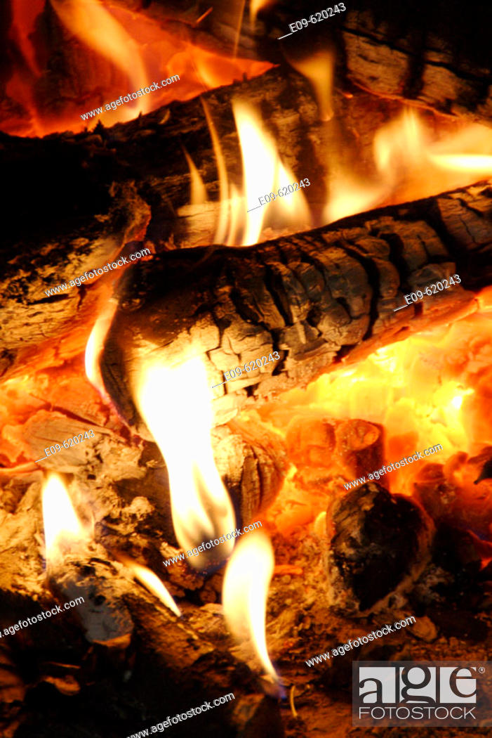 Imagen: detail of fire in fireplace, glowing coals, yellow-white flames at ends of logs and in embers.