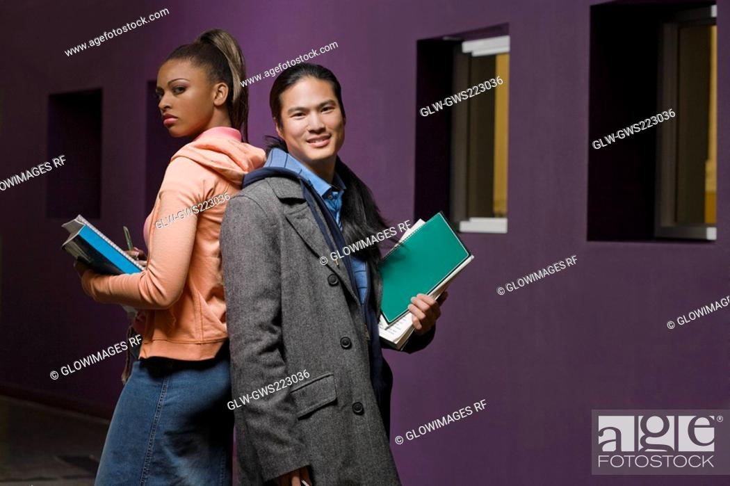 Stock Photo: Young couple standing back to back in a corridor.