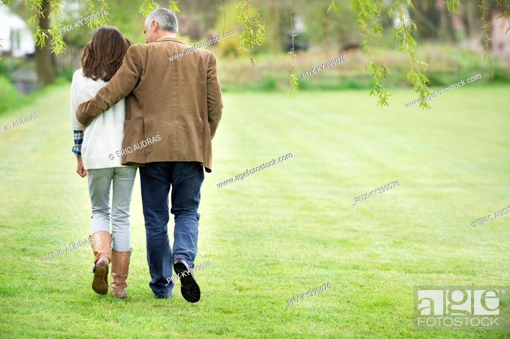 Stock Photo: Man walking with his daughter in a park.