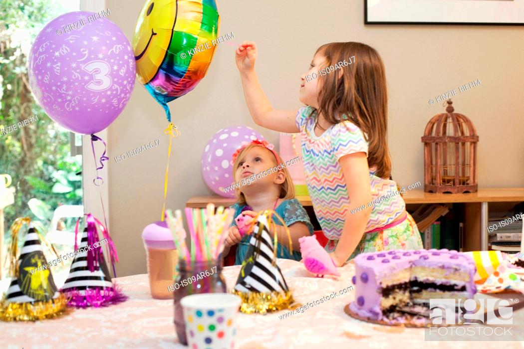 Stock Photo: Two girls sitting at birthday party table with cake playing with balloons.