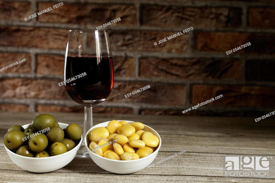 Stock Photo: Red wine glass, olives bowl and lupins bowl on wooden table and red brick background.