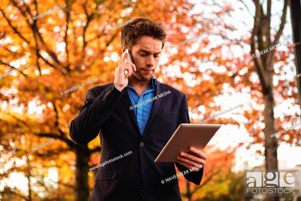 Stock Photo: Businessman talking on mobile phone and holding digital tablet.