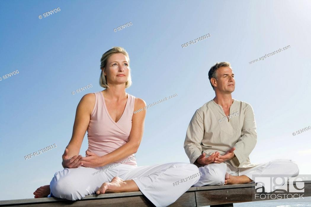 Stock Photo: Mature couple sitting cross-legged on wooden bench outdoors doing yoga.