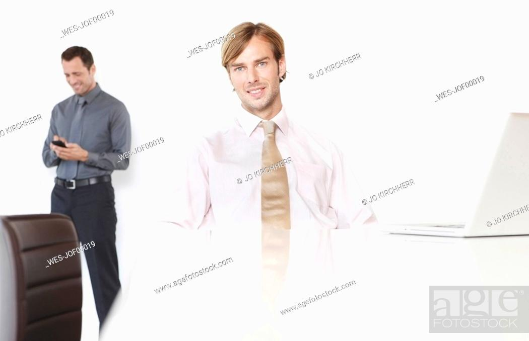 Stock Photo: Germany, Cologne, Two businessmen in conference room, laptop on desk.