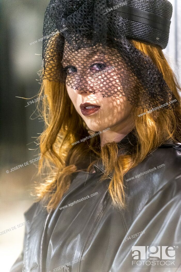 Stock Photo: Portrait of a 25 year old redheaded woman wearing a veiled hat in an urban setting.