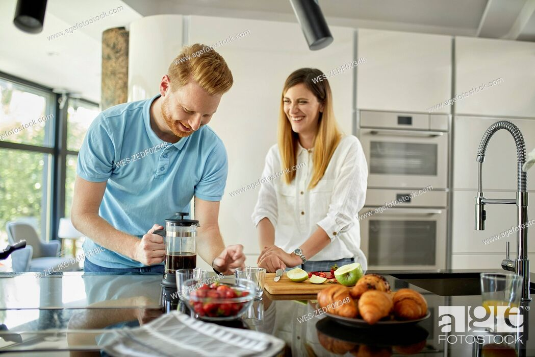 Stock Photo: Couple standing in kitchen, preparing healthy breakfast, chopping fruits.