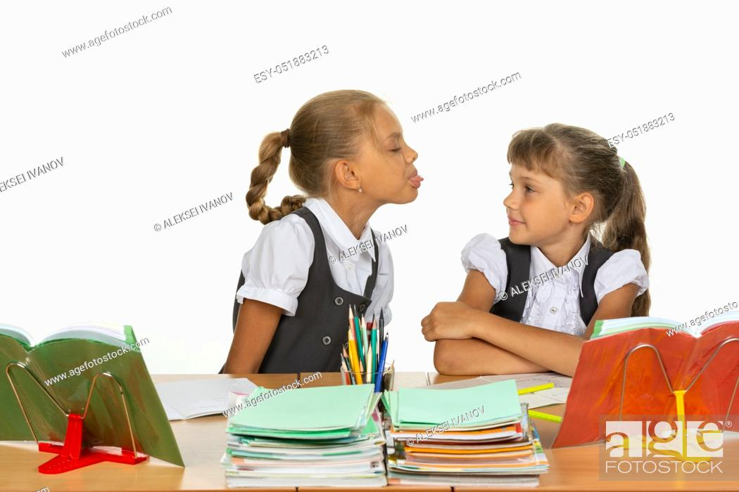 Stock Photo: Girl at her desk showed tongue to another girl.
