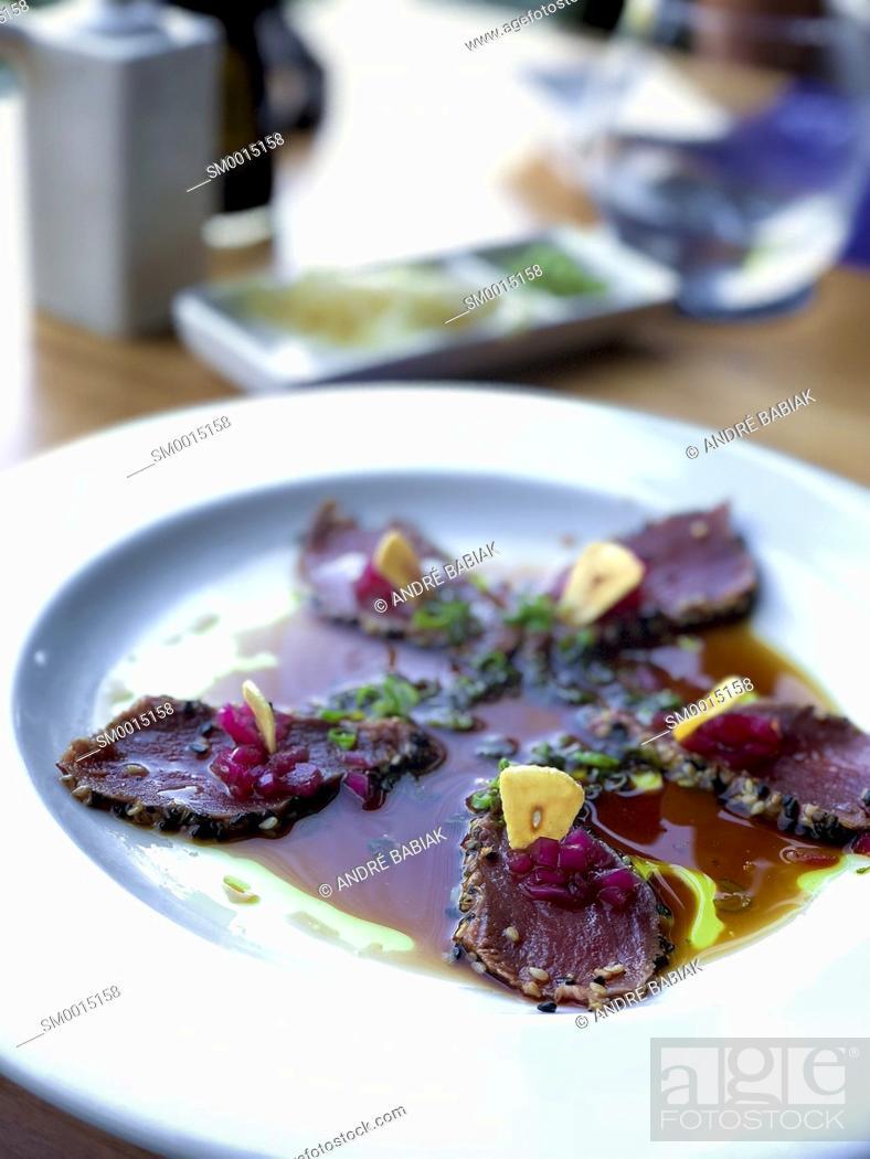 Stock Photo: Tuna Sashimi with slices of fried garlic.