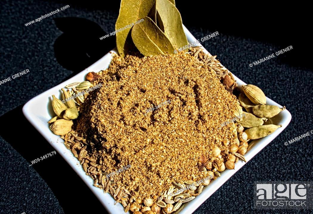 Stock Photo: Homemade garam masala spice mix in a white small dish on a dark background close up.