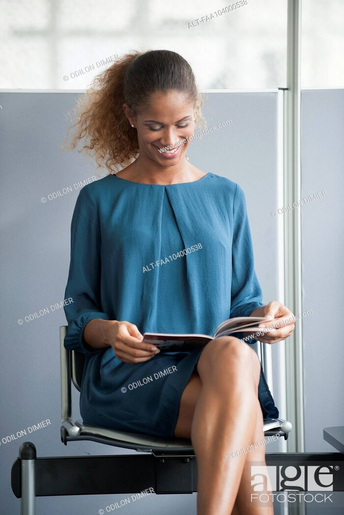 Stock Photo: Woman reading in waiting room, smiling cheerfully.