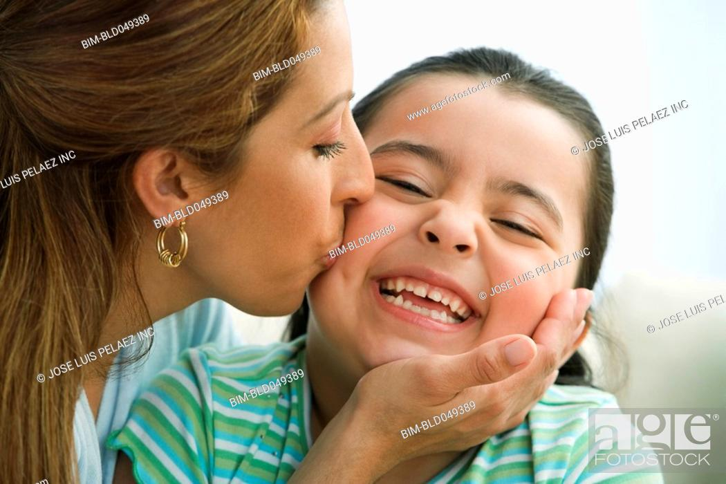 Stock Photo: Hispanic mother kissing daughter on cheek.
