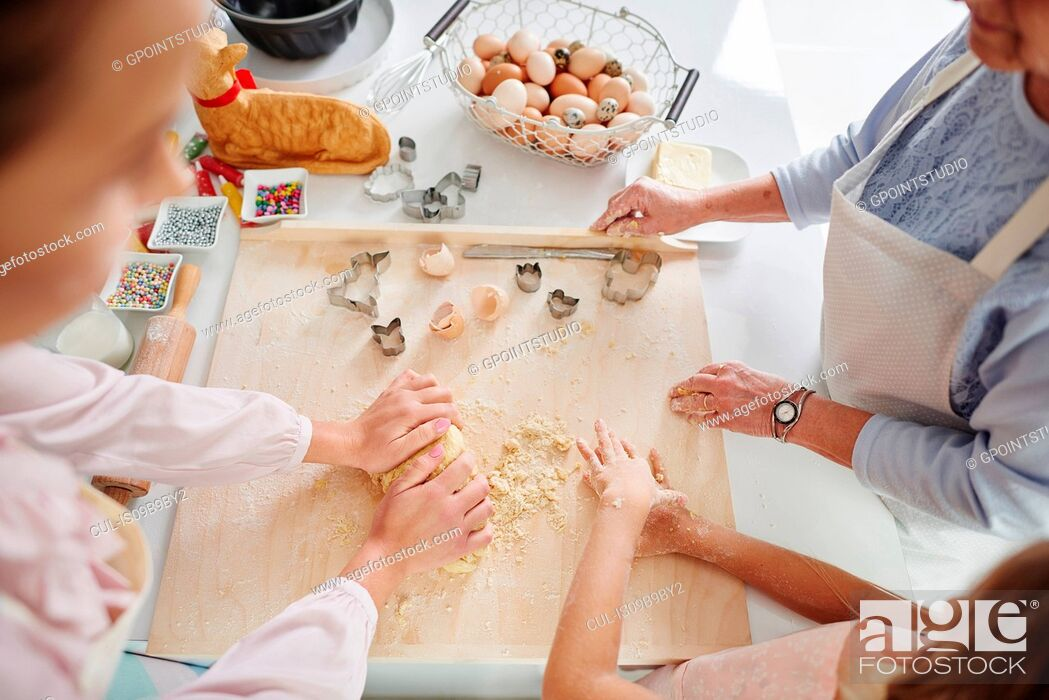 Stock Photo: Cropped shot of girl, mother and grandmother easter baking at kitchen counter.