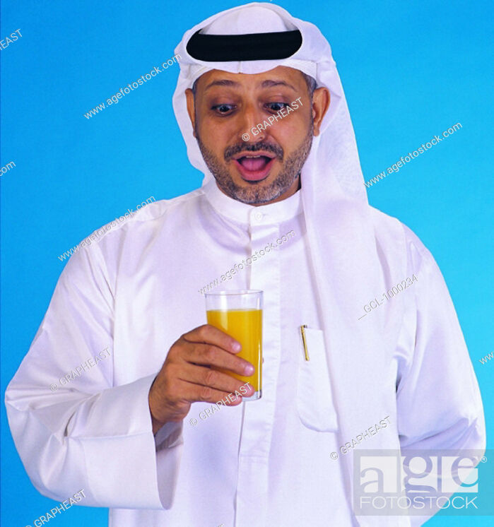 Stock Photo: Arab man holding a glass with orange juice.