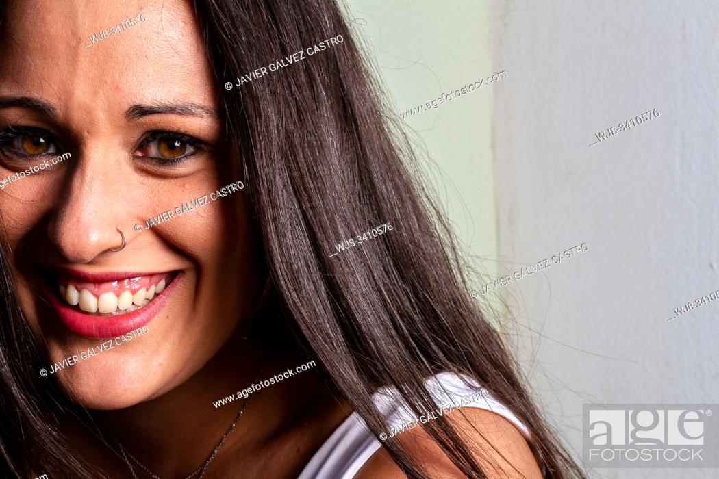 Stock Photo: studio lighting portrait of a young woman smiling with expressive eyes.