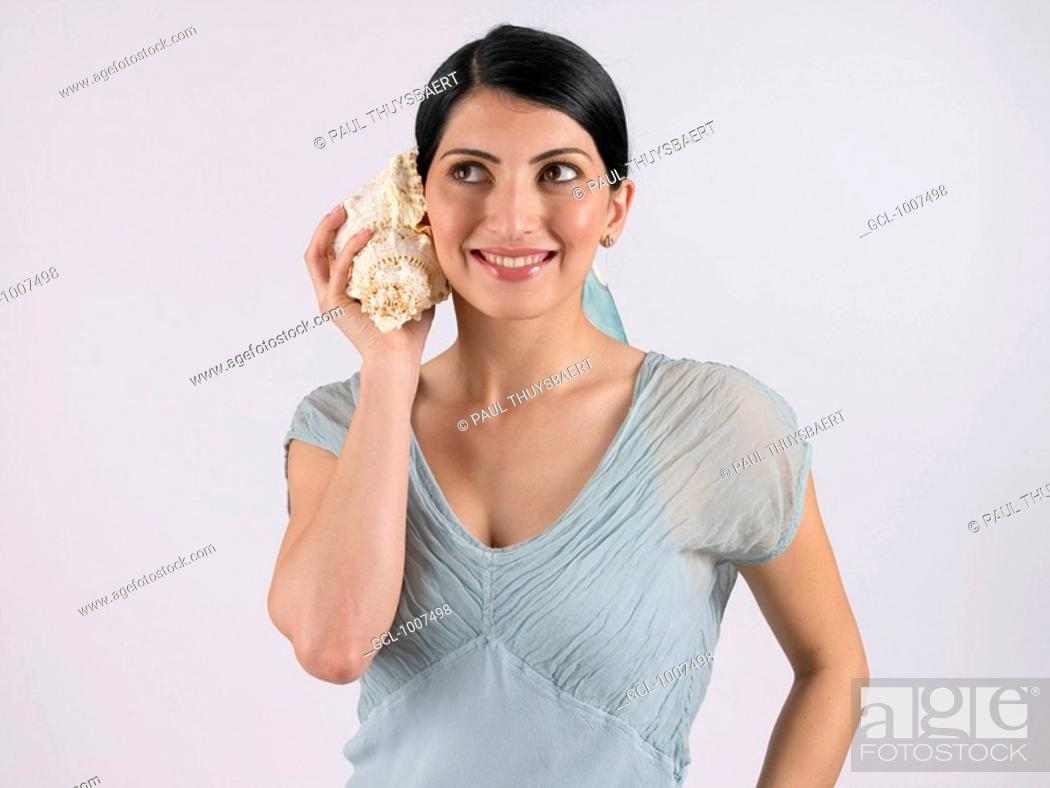 Stock Photo: Woman holding seashell to her ear.