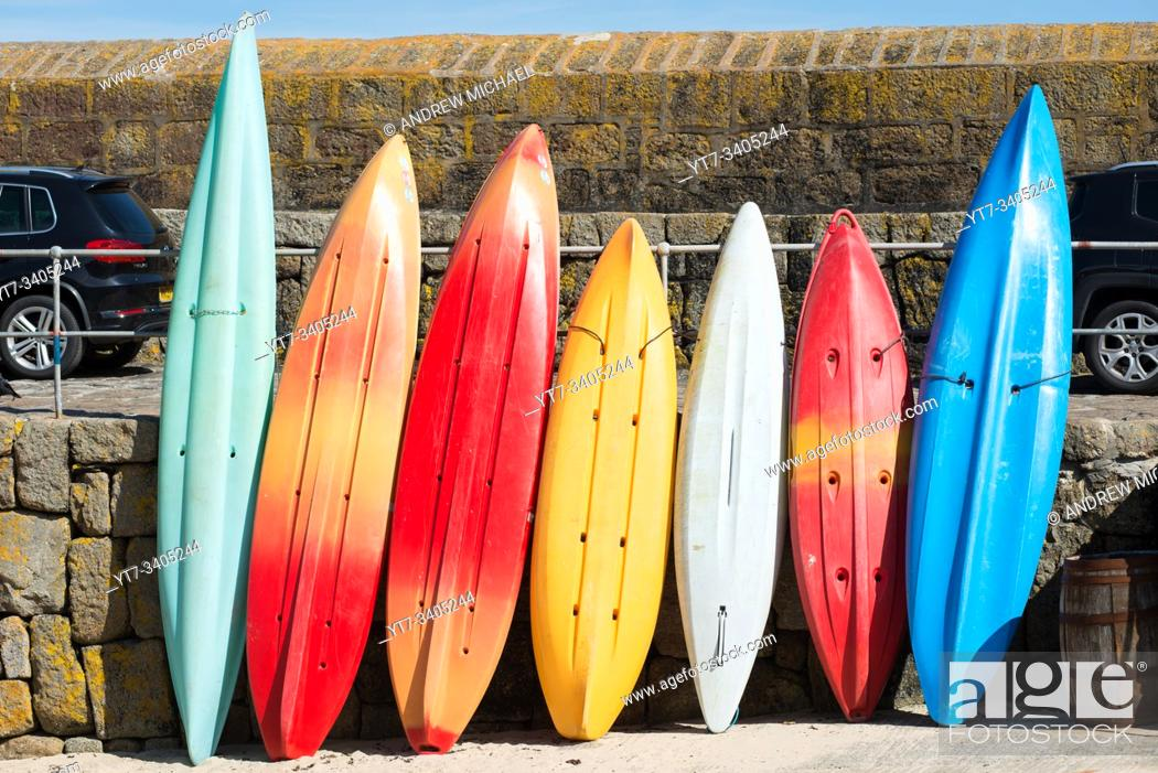 Stock Photo: Colourful kayaks lined up at Mousehole in West Cornwall, England, UK.