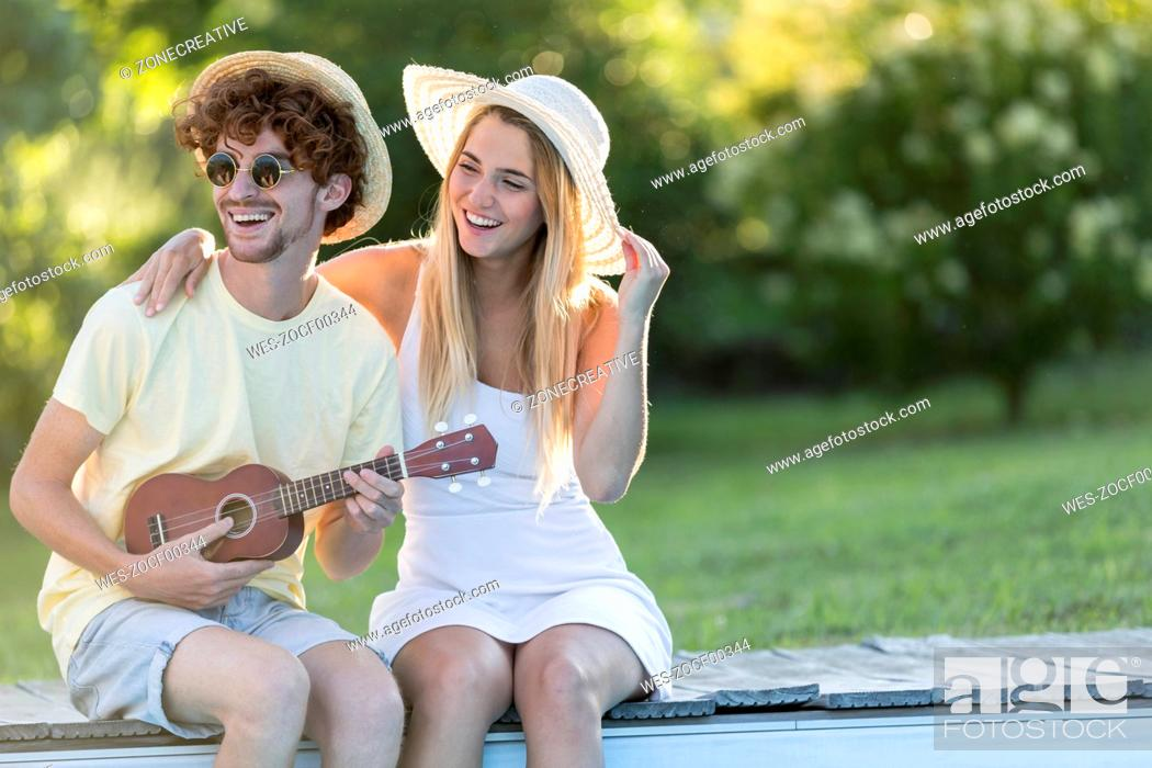 Imagen: Laughing young couple relaxing at pool edge.
