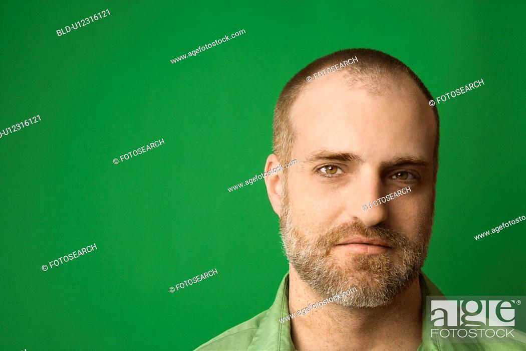 Stock Photo: Head shot of Caucasian man with beard and receding hairline against green background.