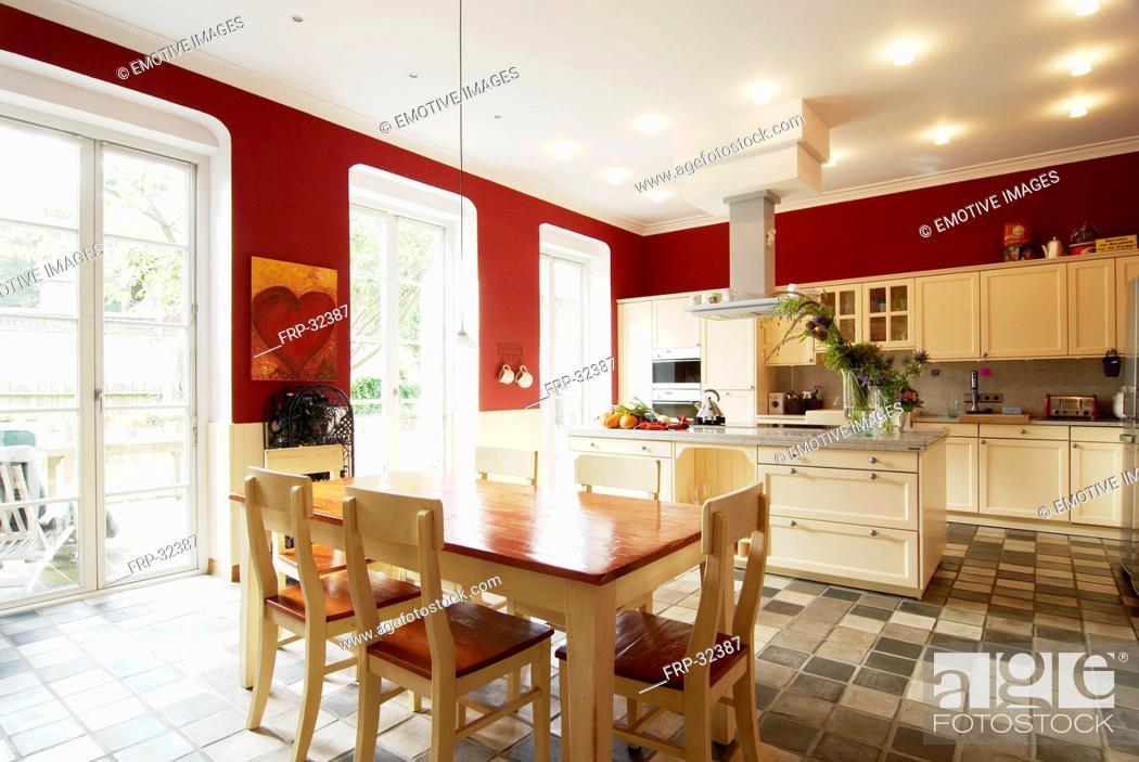 Stock Photo: Open plan kitchen with dining area and tiled floor.