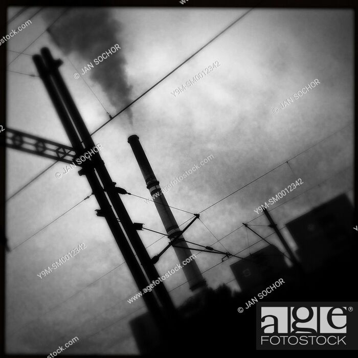 Stock Photo: A smoking chimney of the Prunérov I coal-fired power plant seen from the train passing through the industrial area in the north of the Czech Republic.